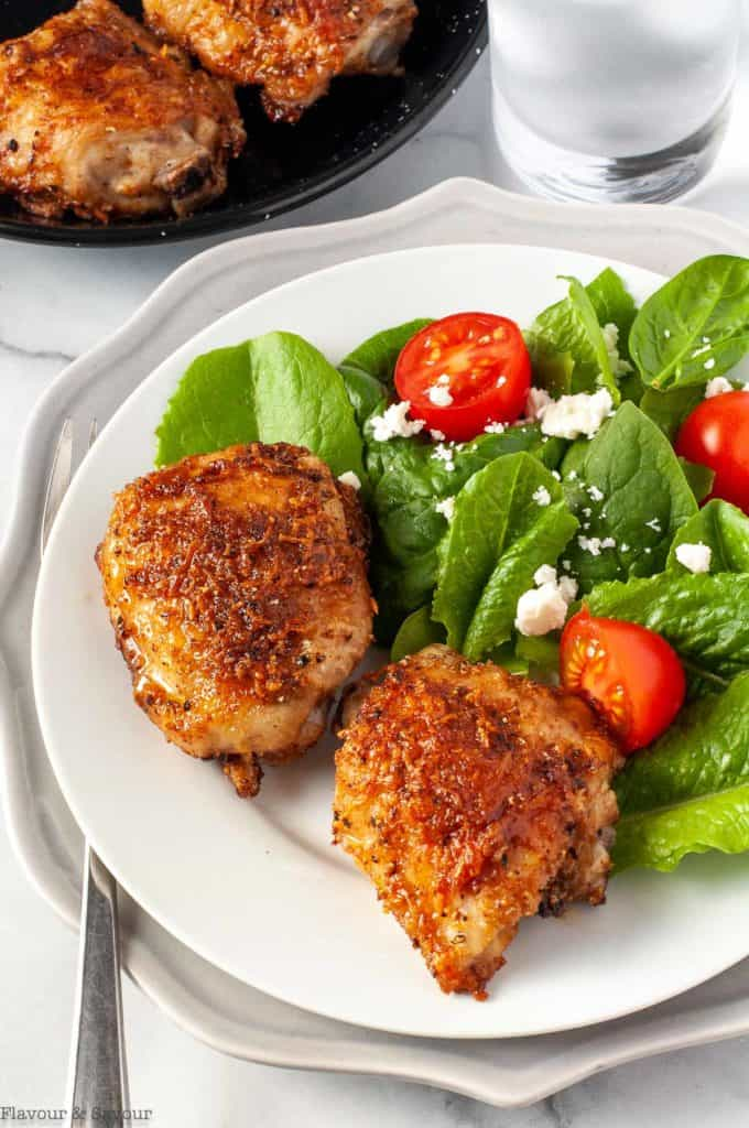 Garlic Parmesan Chicken Thighs on a plate with a green salad