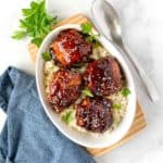 Overhead image of Instant Pot Sticky Chicken Thighs in a bowl with a serving spoon