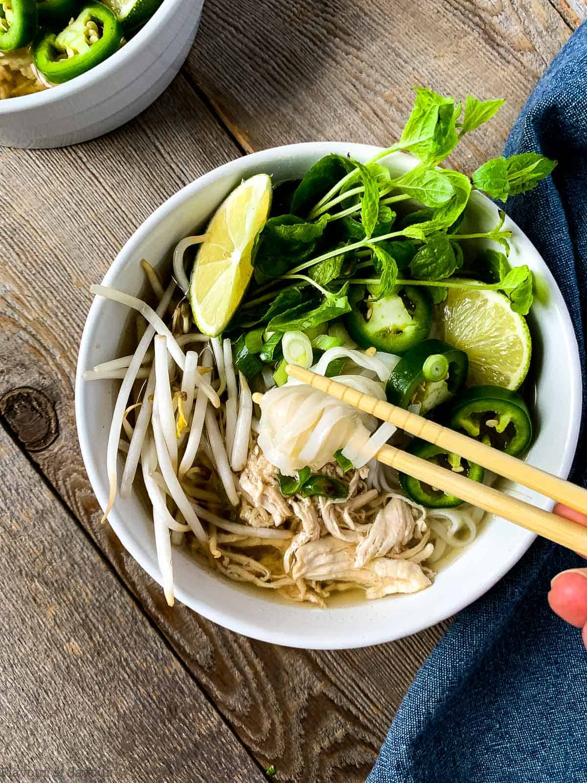 Lifting noodles from Vietnamese Chicken Noodle Soup (Pho  Ga) with chopsticks
