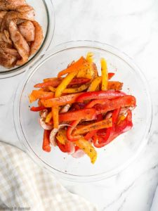 A bowl of sliced bell peppers and one of sliced chicken tossed with oil and fajita seasoning