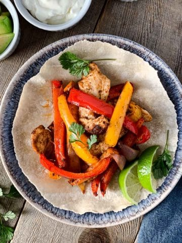 Overhead image of Chicken Fajitas on a blue plate with avocado and lime