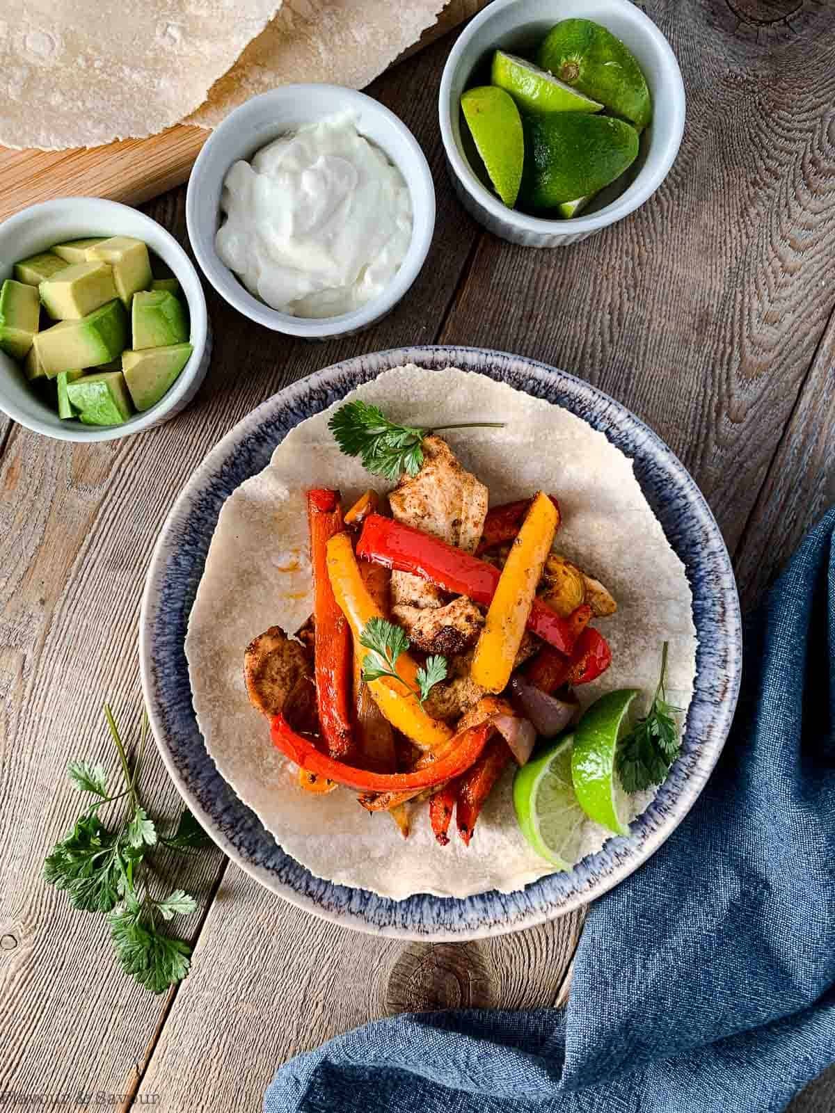 Air Fryer Chicken Fajitas with avocado, sour cream and lime wedges