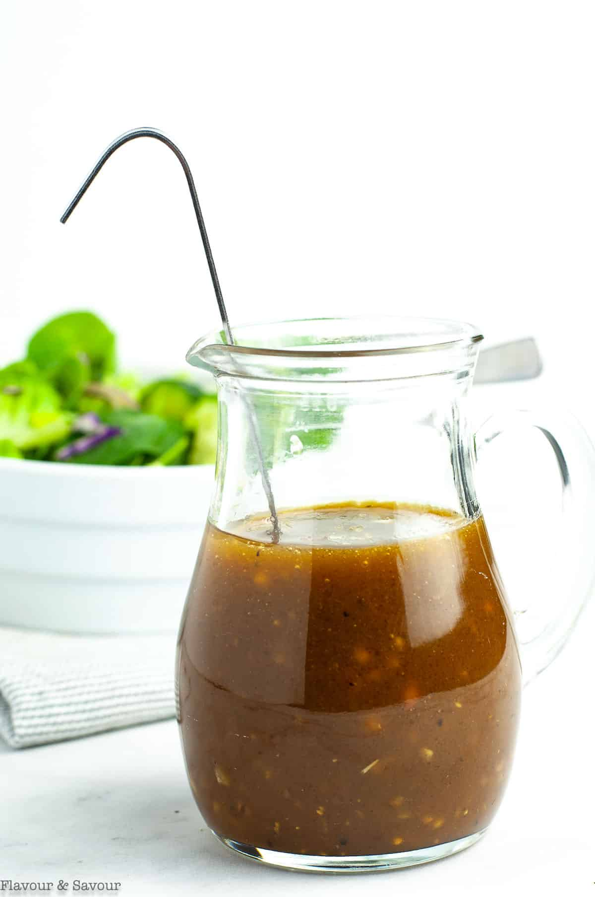 A small pitcher of Maple Balsamic Dressing with a salad
