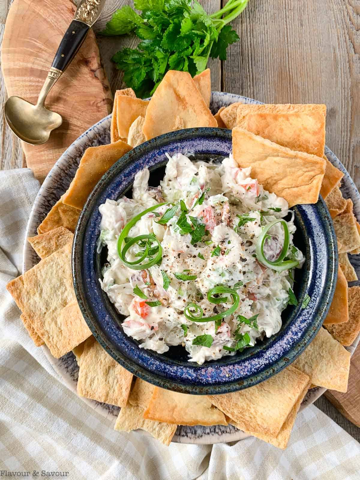 Overhead view of a bowl of cold crab dip surrounded by pita chips
