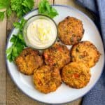 Salmon Patties on a round plate with a bowl of aioli, overhead view