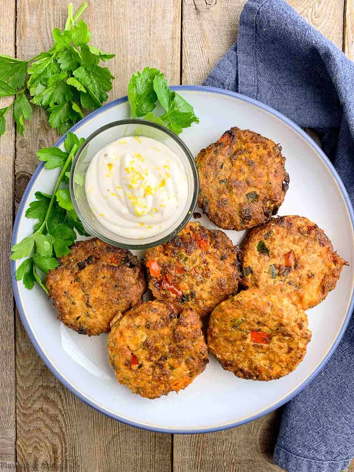 Overhead view of 6 salmon cakes on a plate with lemon aioli dip
