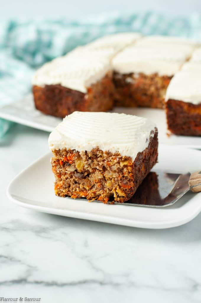 A square of carrot cake with the remaining cake in the background
