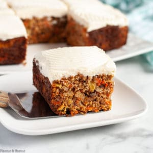 A square of grain-free carrot cake with cream cheese frosting .