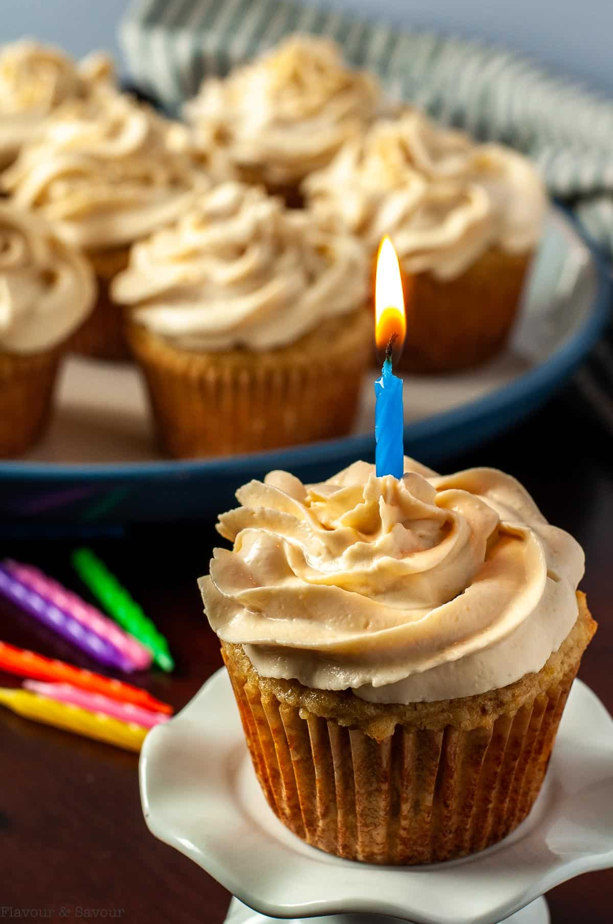 A frosted banana cupcake with a lit birthday candle