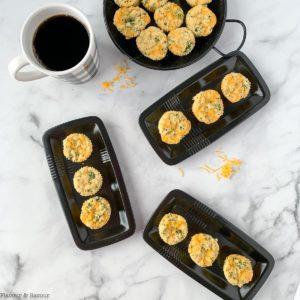 Gluten-free Broccoli Cheddar Muffins on small black plates.