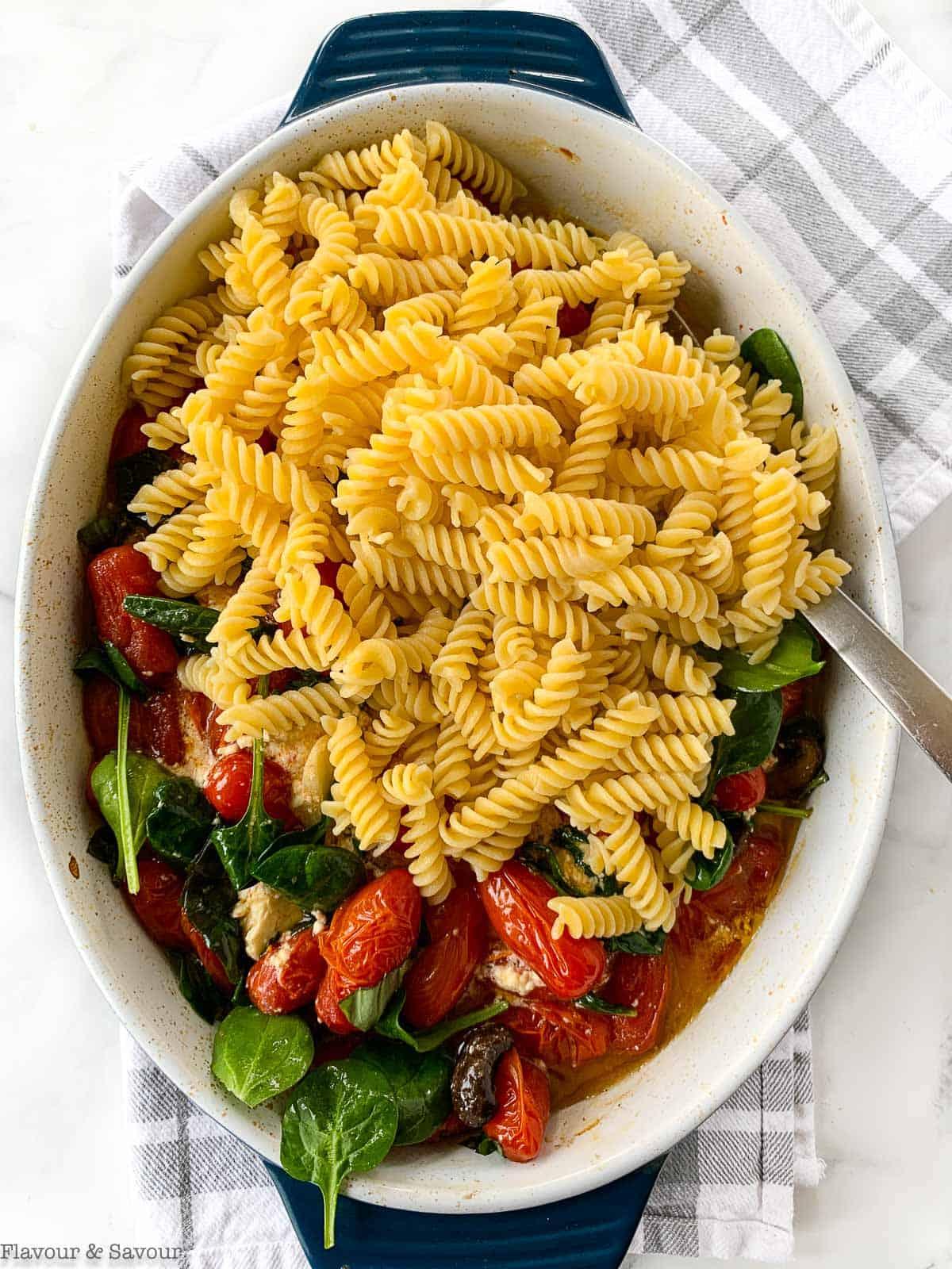 adding pasta to feta pasta tomato bake