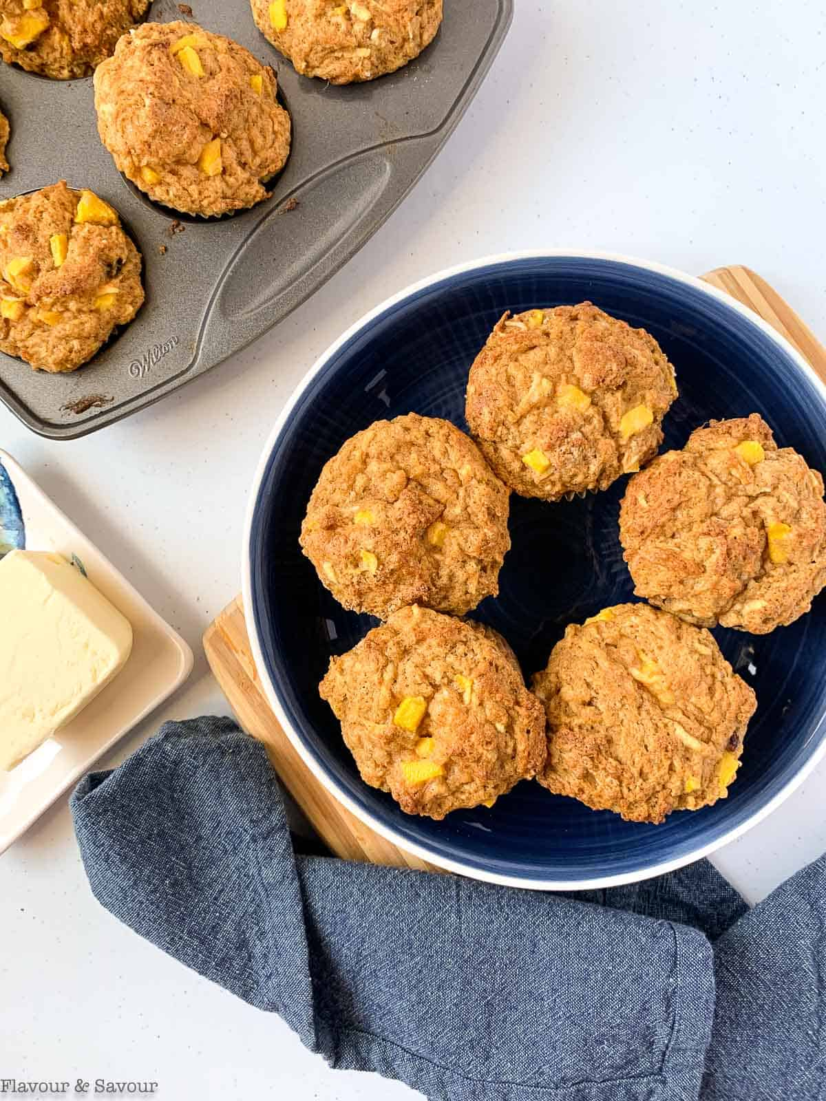 Gluten-free Mango Muffins in a bowl with a butter dish beside