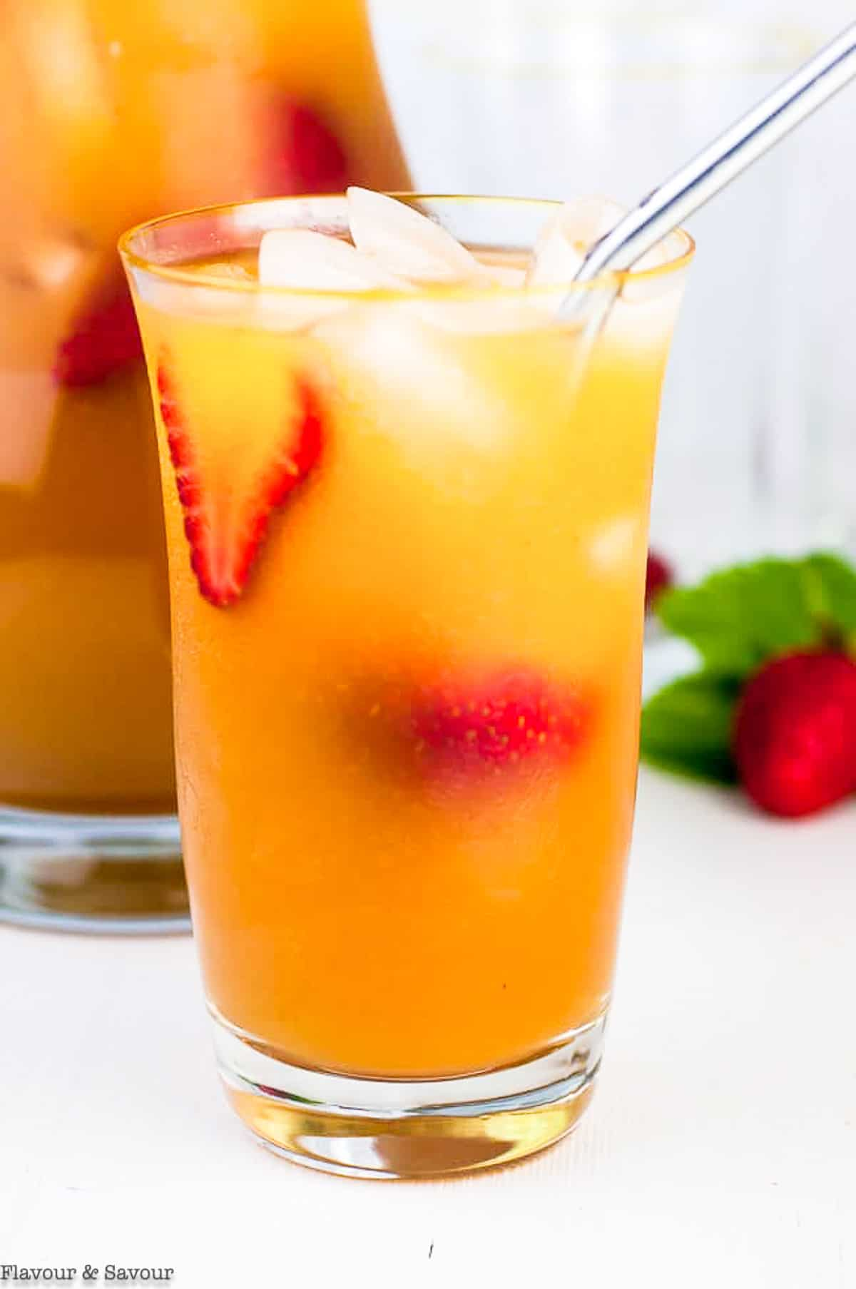 a tall glass of Peach Iced Tea with a metal straw
