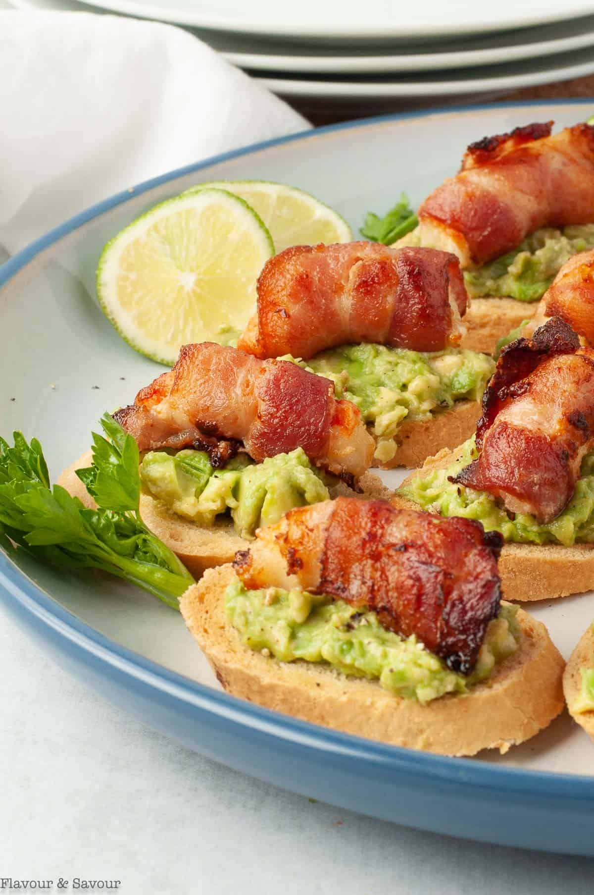 A plate filled with Bacon-Wrapped Shrimp (or Prawn) Tapas, a crostini topped with avocado and a bacon wrapped shrimp.