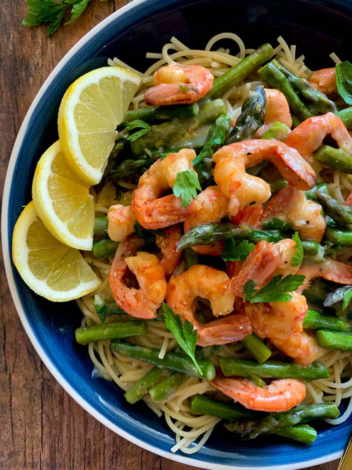 a large bowl of shrimp linguine with asparagus and lemon