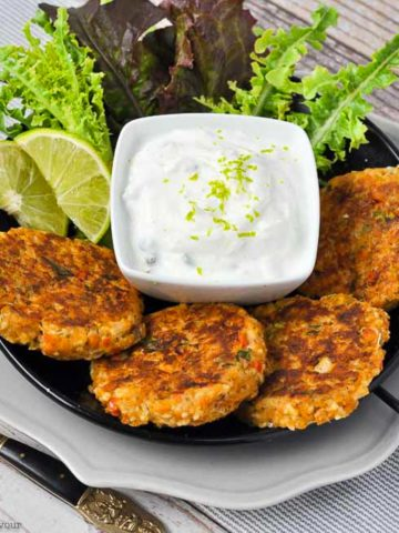 four salmon patties on a plate with a small bowl of lime sauce and lime wedges