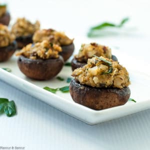 Mushrooms stuffed with blue cheese, garlic and herbs on a white narrow serving dish
