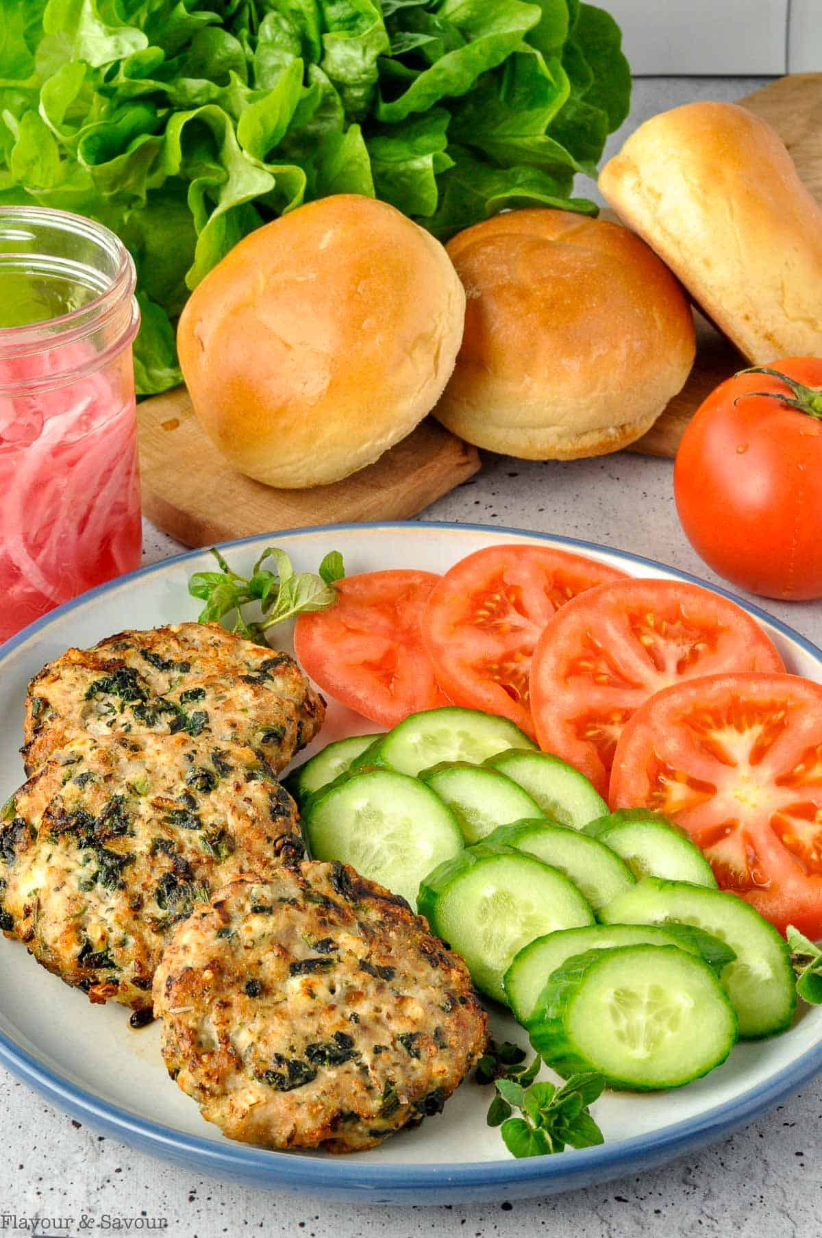 Ingredients for Greek Chicken Burgers arranged on a plate with buns and lettuce.