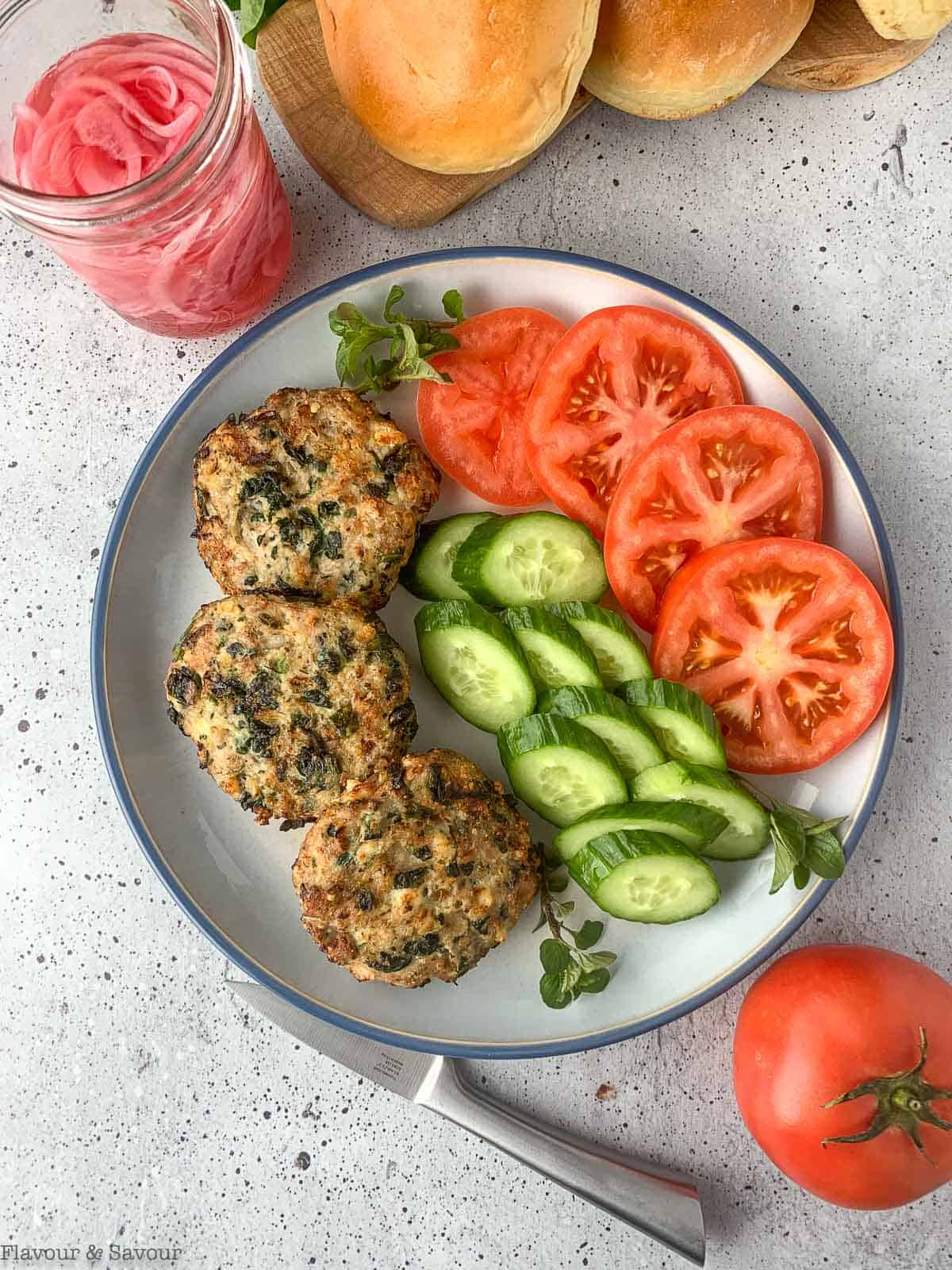 Air Fried Greek Chicken Burgers on a palte with sliced tomatoes and cucumbers