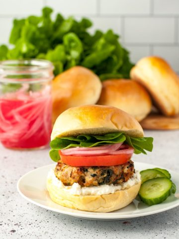 Greek Chicken Burger with spinach and feta on a brioche bun with lemon-garlic feta spread, sliced tomato, pickled red onions and lettuce leaves.