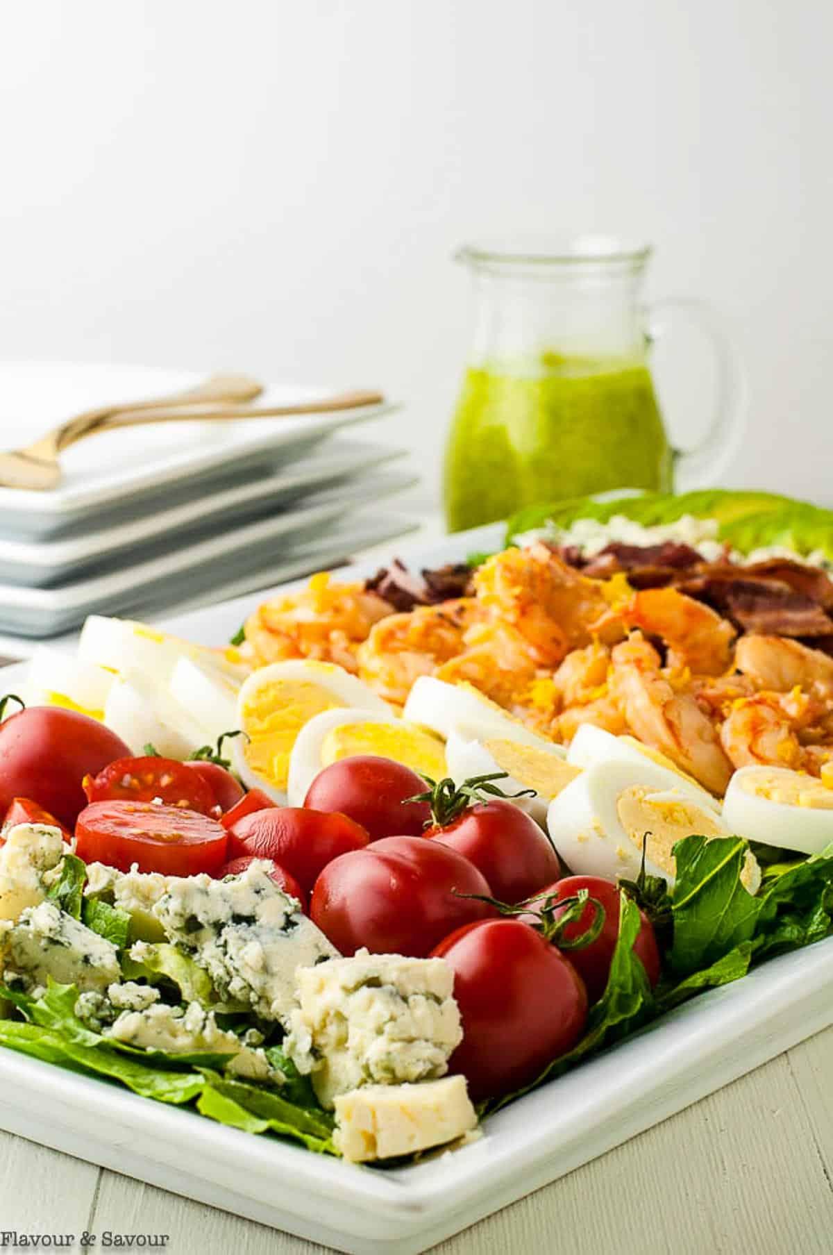 Lemon Garlic Shrimp Cobb Salad on a platter with a pitcher of dressing