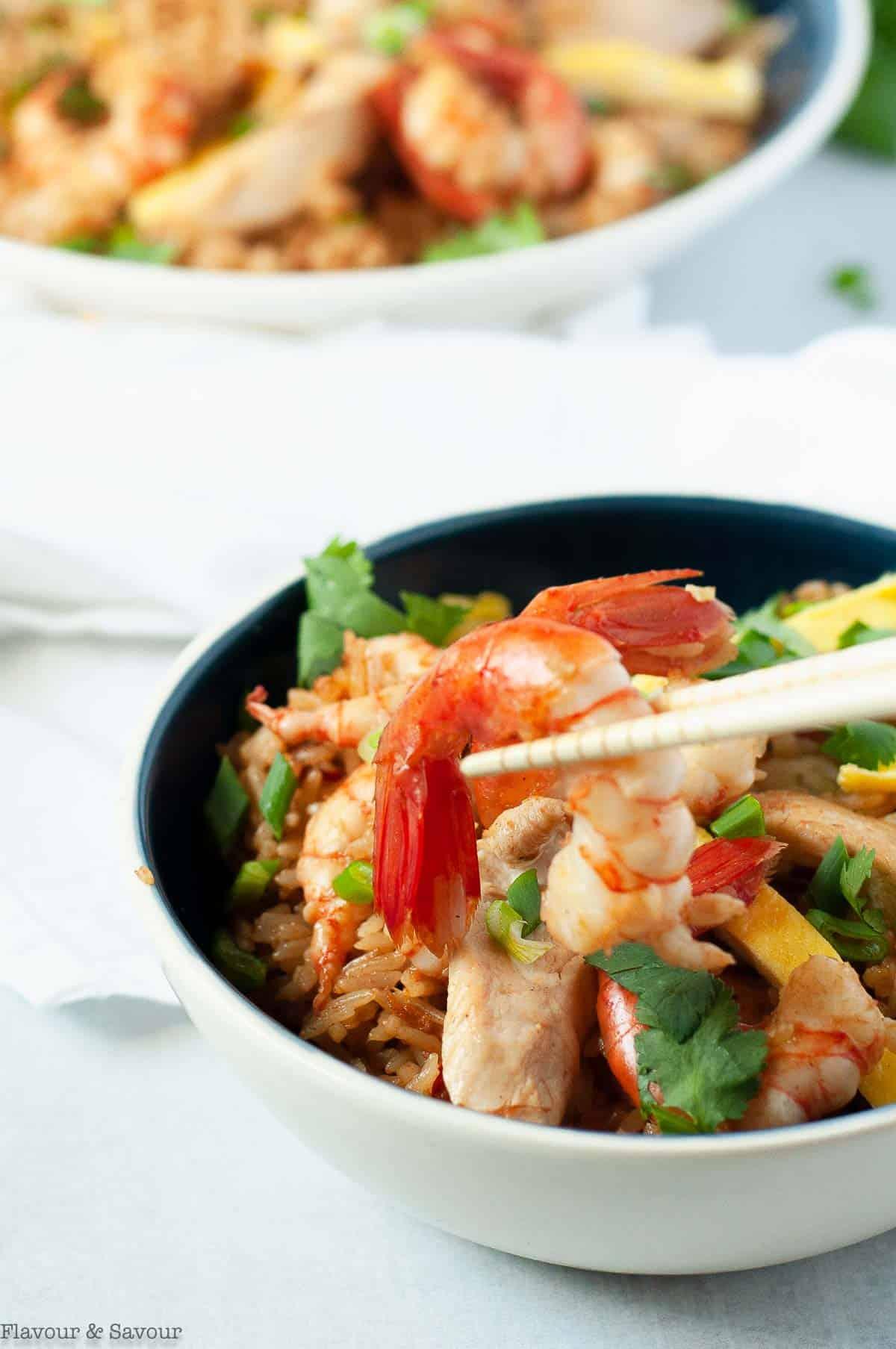 Close up view of a prawn with chopsticks from a bowl of Nasi Goreng