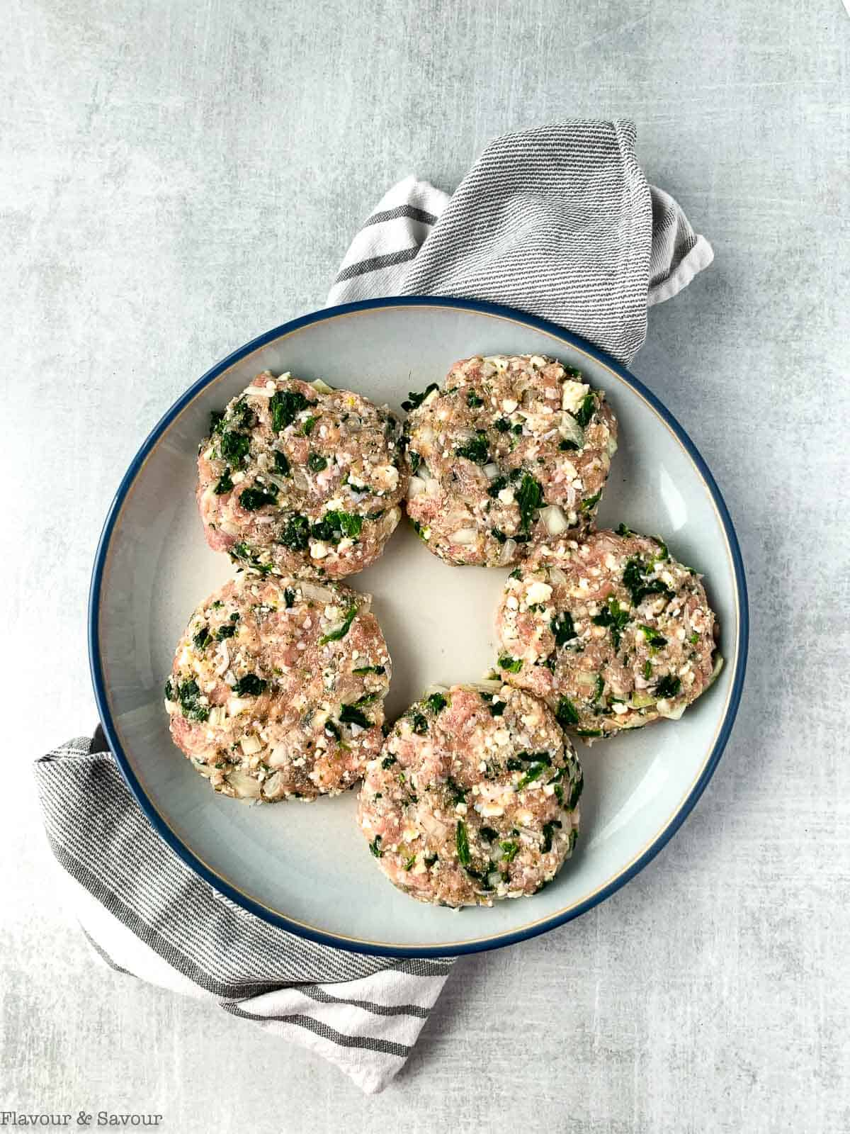 Five uncooked Greek Chicken Burger patties on a plate.