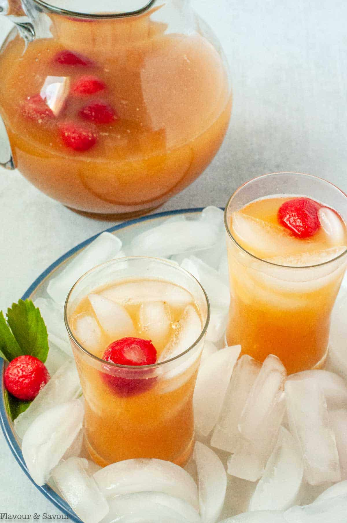 a pitcher of peach tea with two glasses on ice