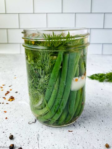 a jar of refrigerator pickled green beans on a countertop