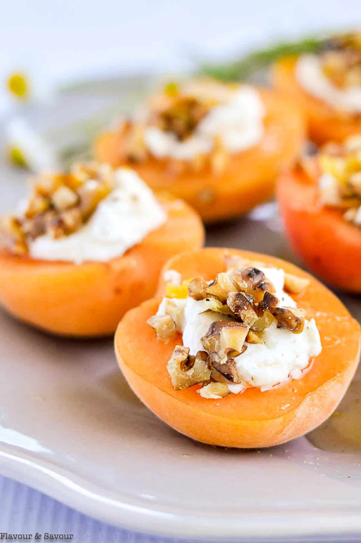 Close up view of fresh apricot appetizer with goat cheese and honey