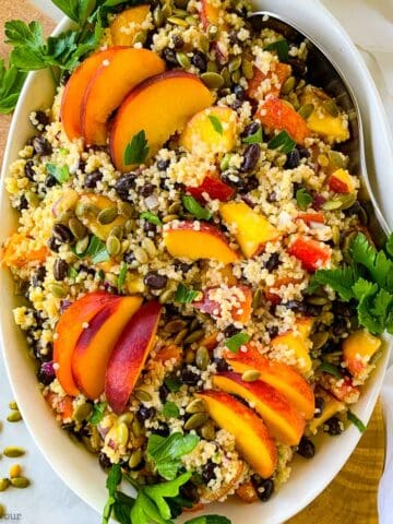 a bowl of quinoa black bean salad with peaches and pumpkin seeds