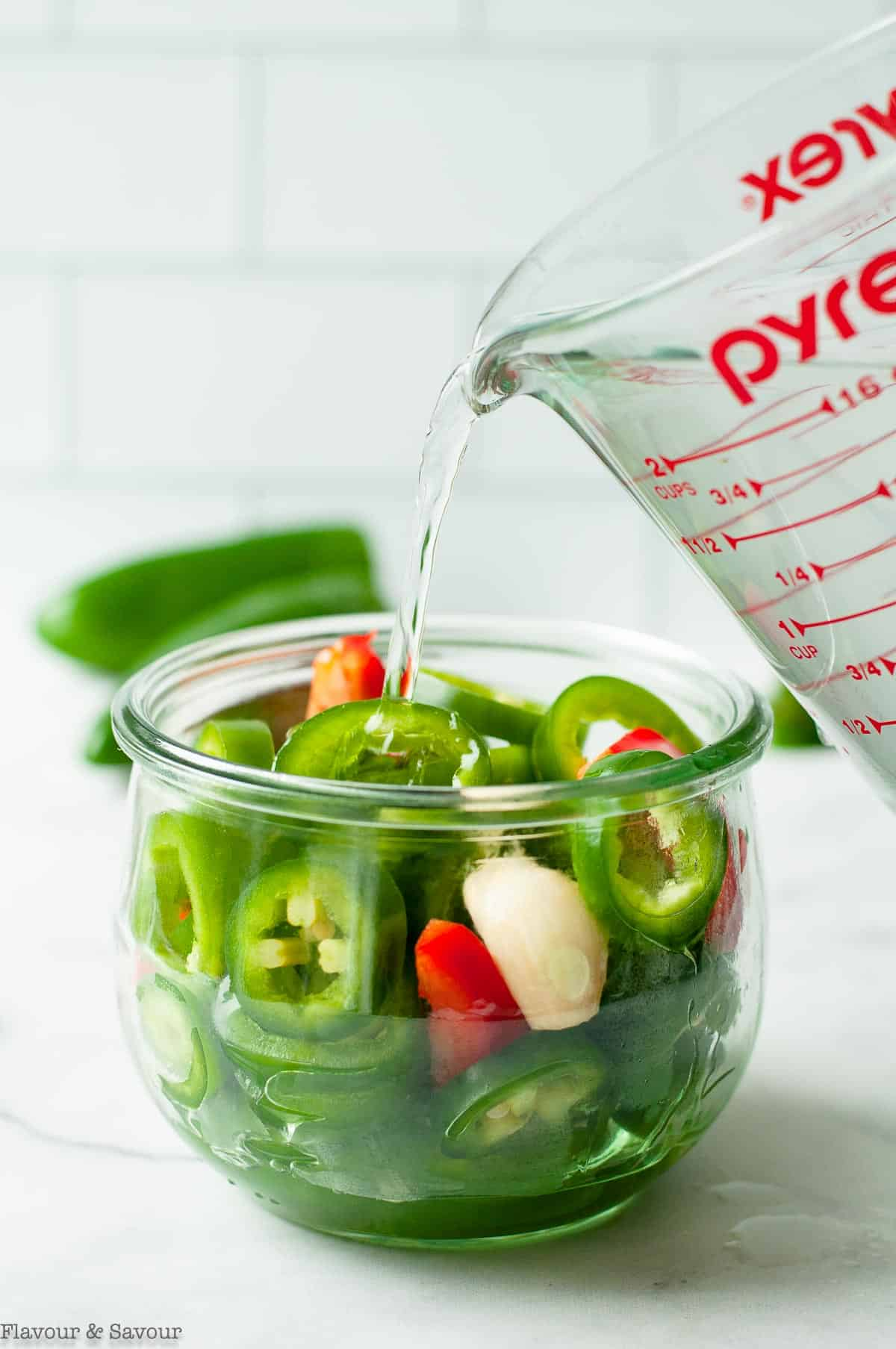 pouring brine on jalapeño pepper slices in a Weck jar