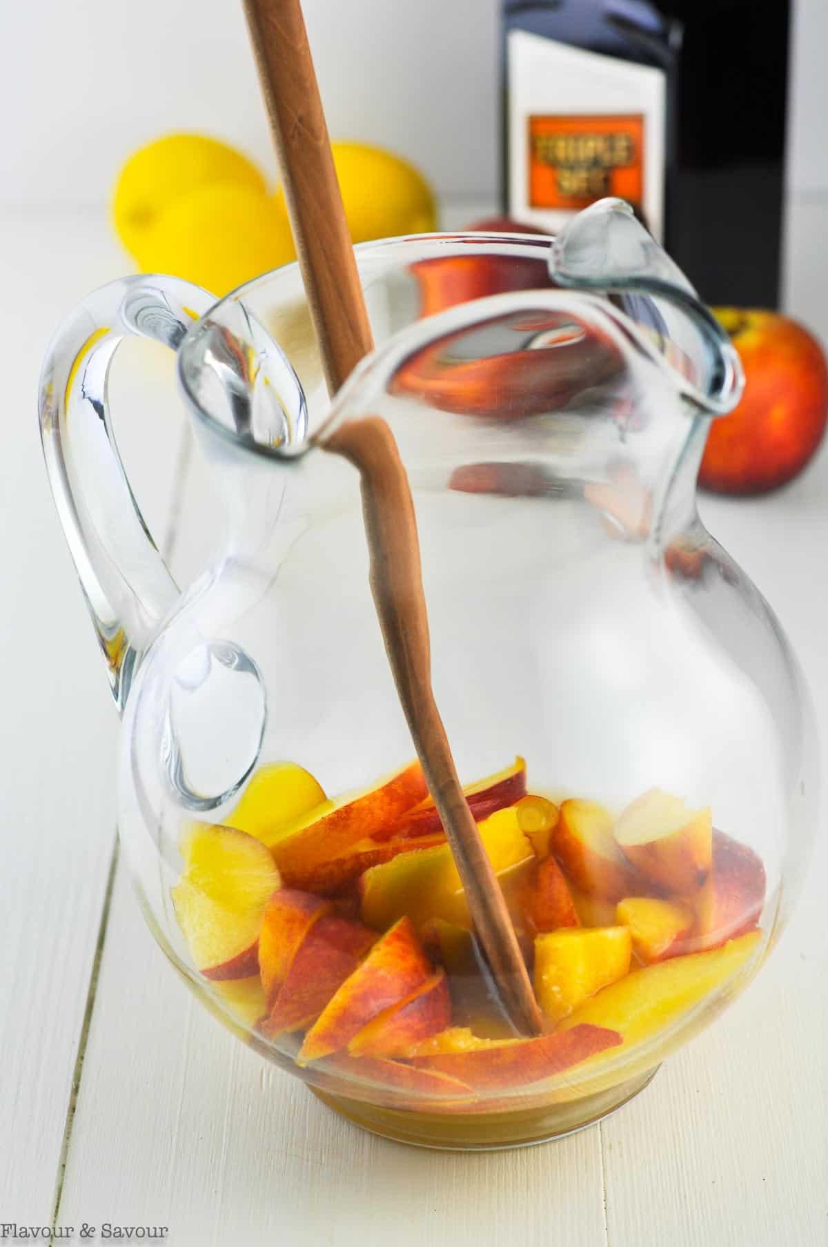 adding fresh peaches to a pitcher for peach sangria