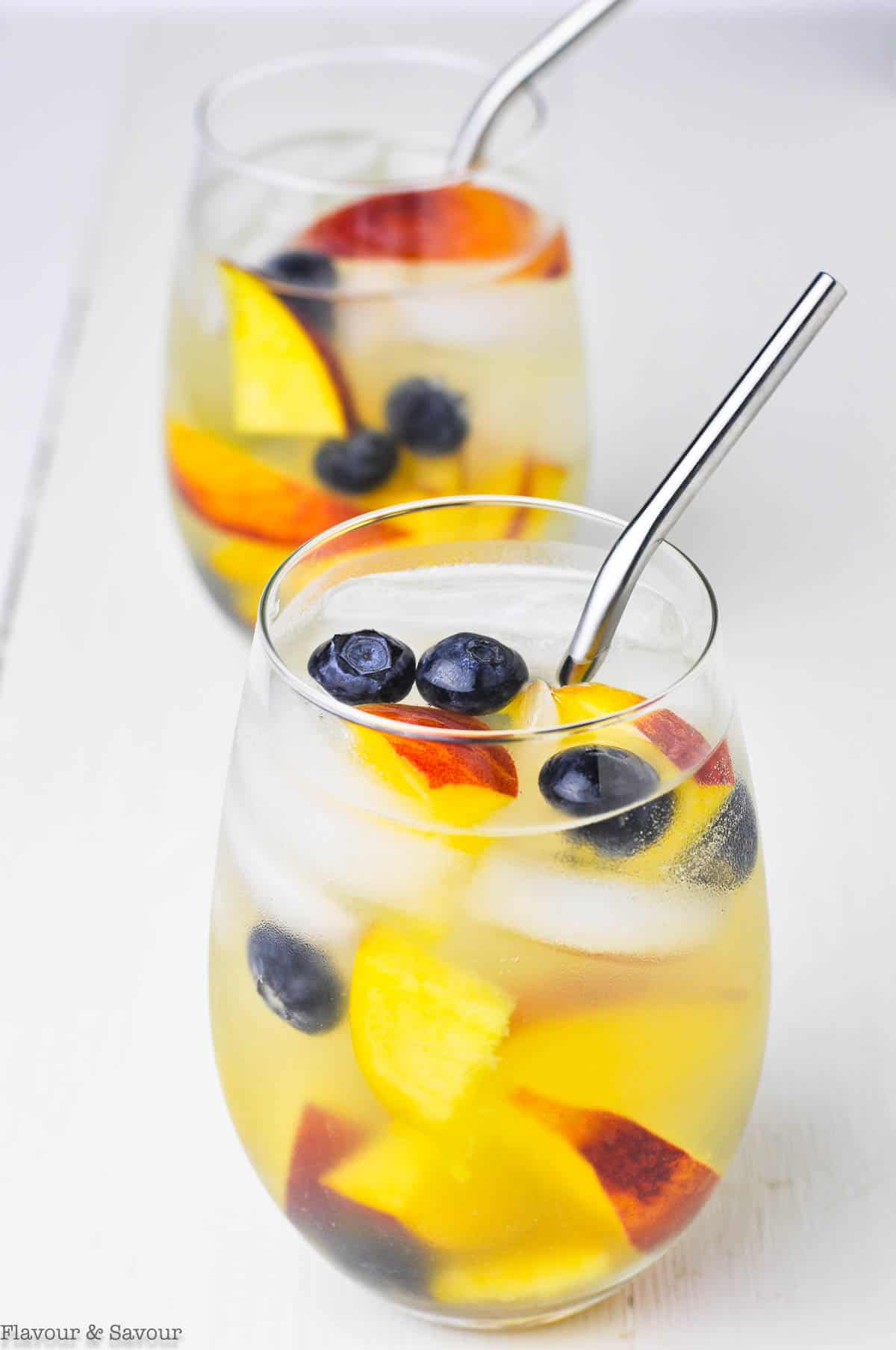 two glasses of white wine peach sangria with blueberries
