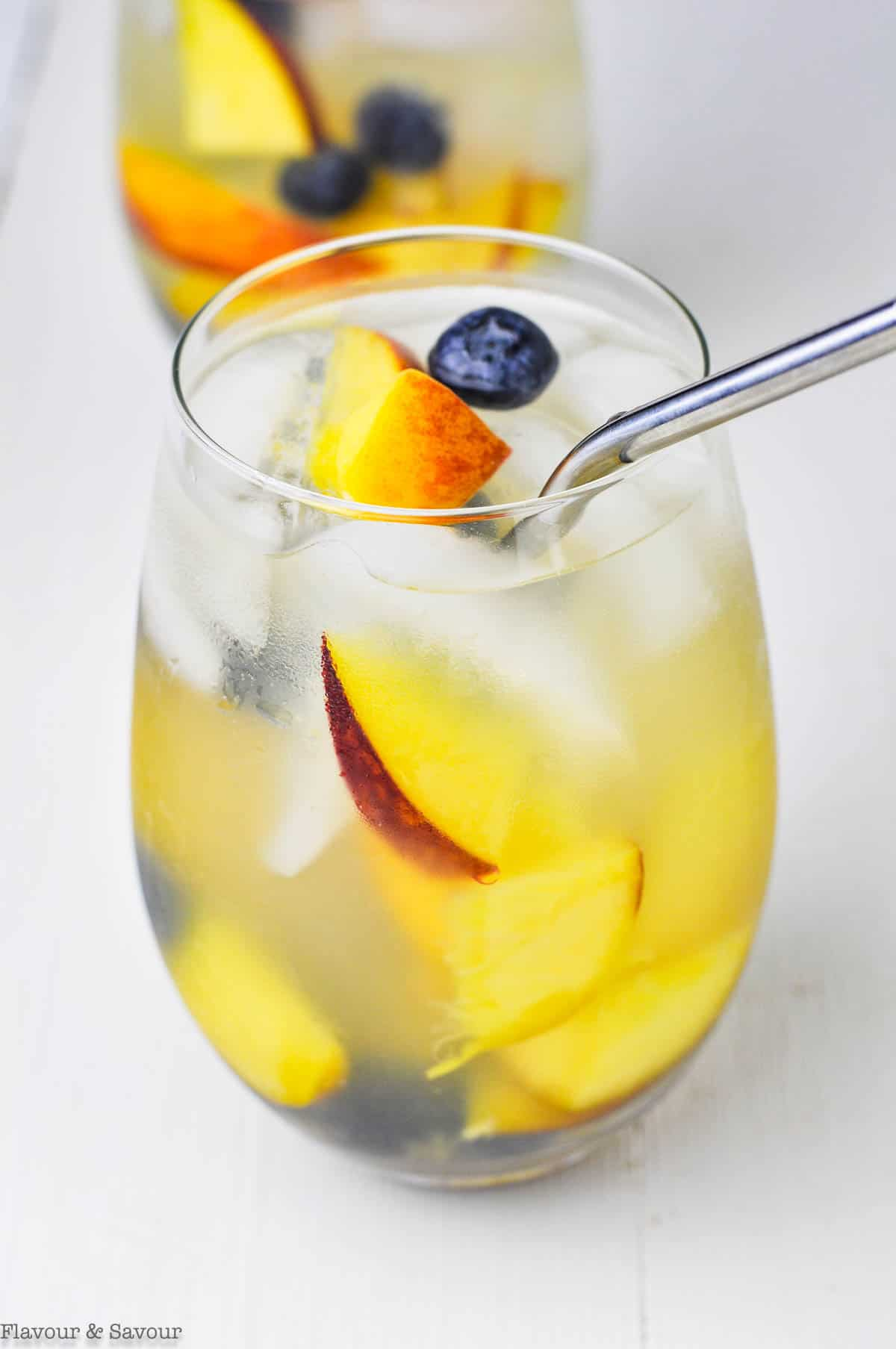 Close up view of a glass of peach sangria with a straw