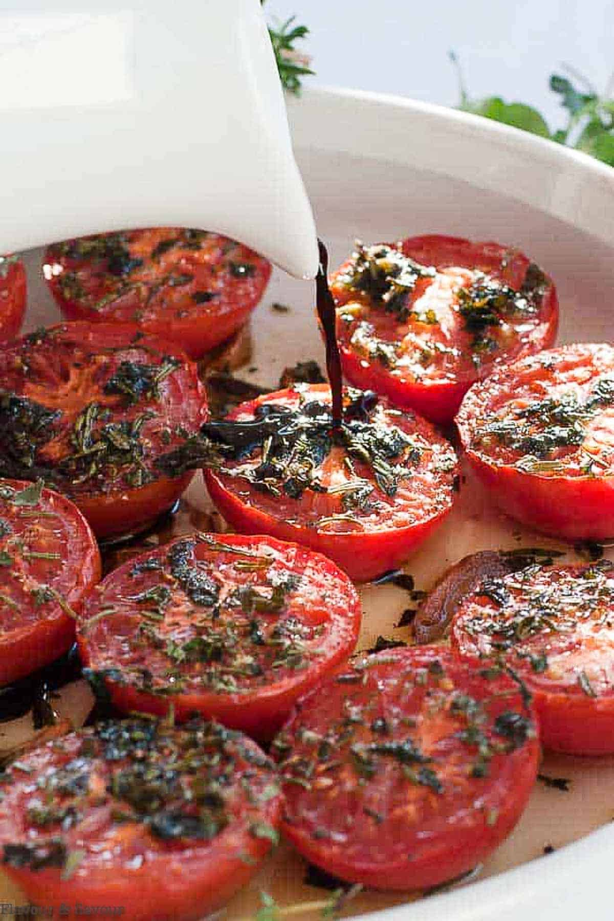 Drizzling balsamic vinegar on broiled Italian tomatoes with garlic and herbs