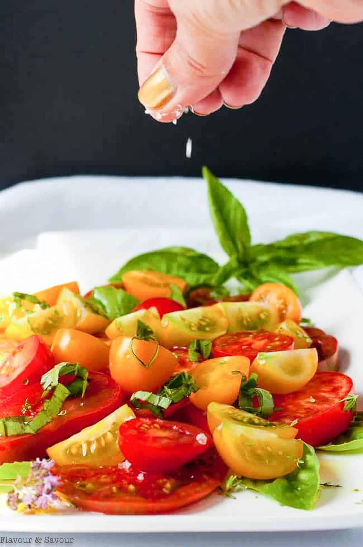 sprinkling coarse salt on Heirloom Tomato Salad with Feta Cheese