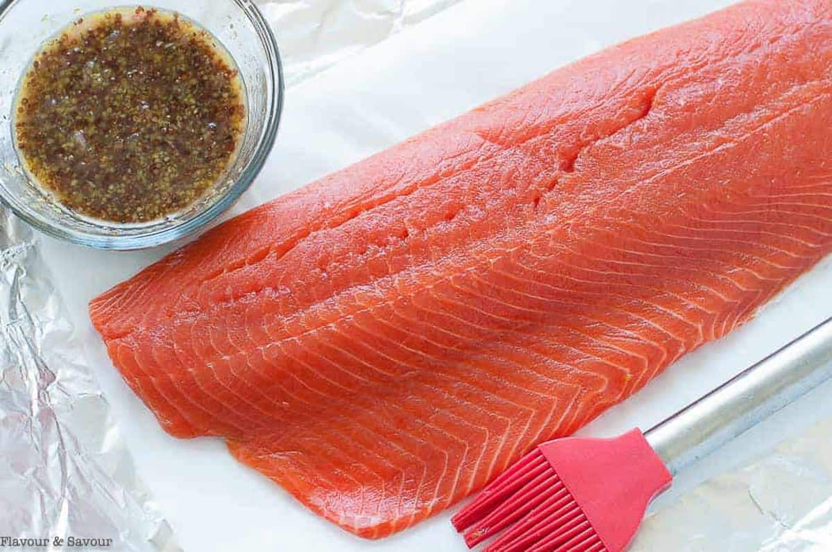 a wild salmon fillet and a small bowl of honey mustard glaze