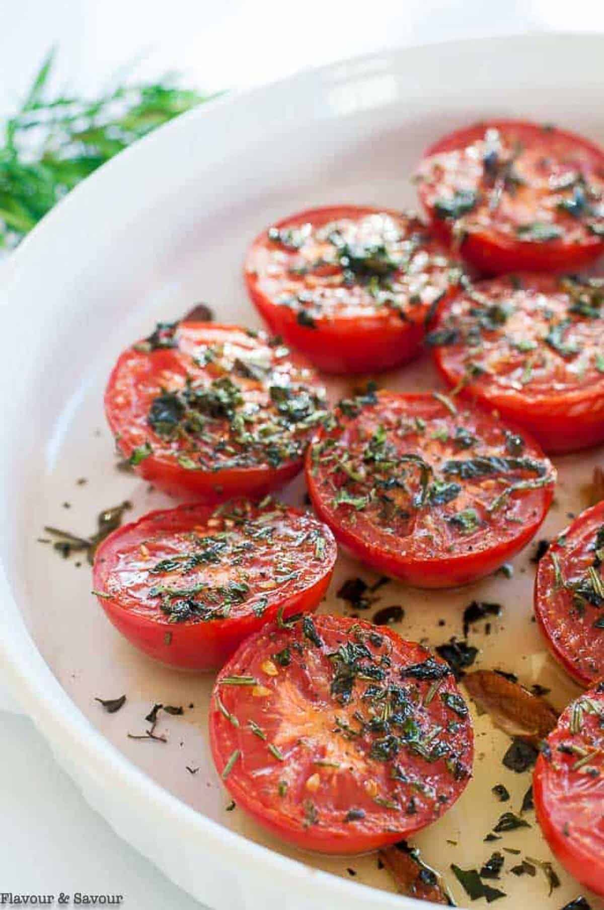 a round baking dish with tomato halves, broiled with garlic and herbs