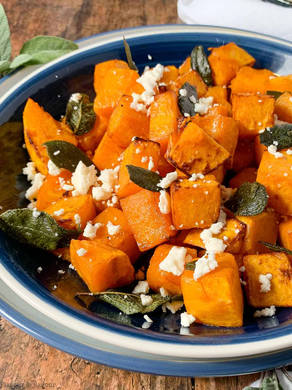 cubes of air fried butternut squash with feta cheese crumbles and toasted sage leaves