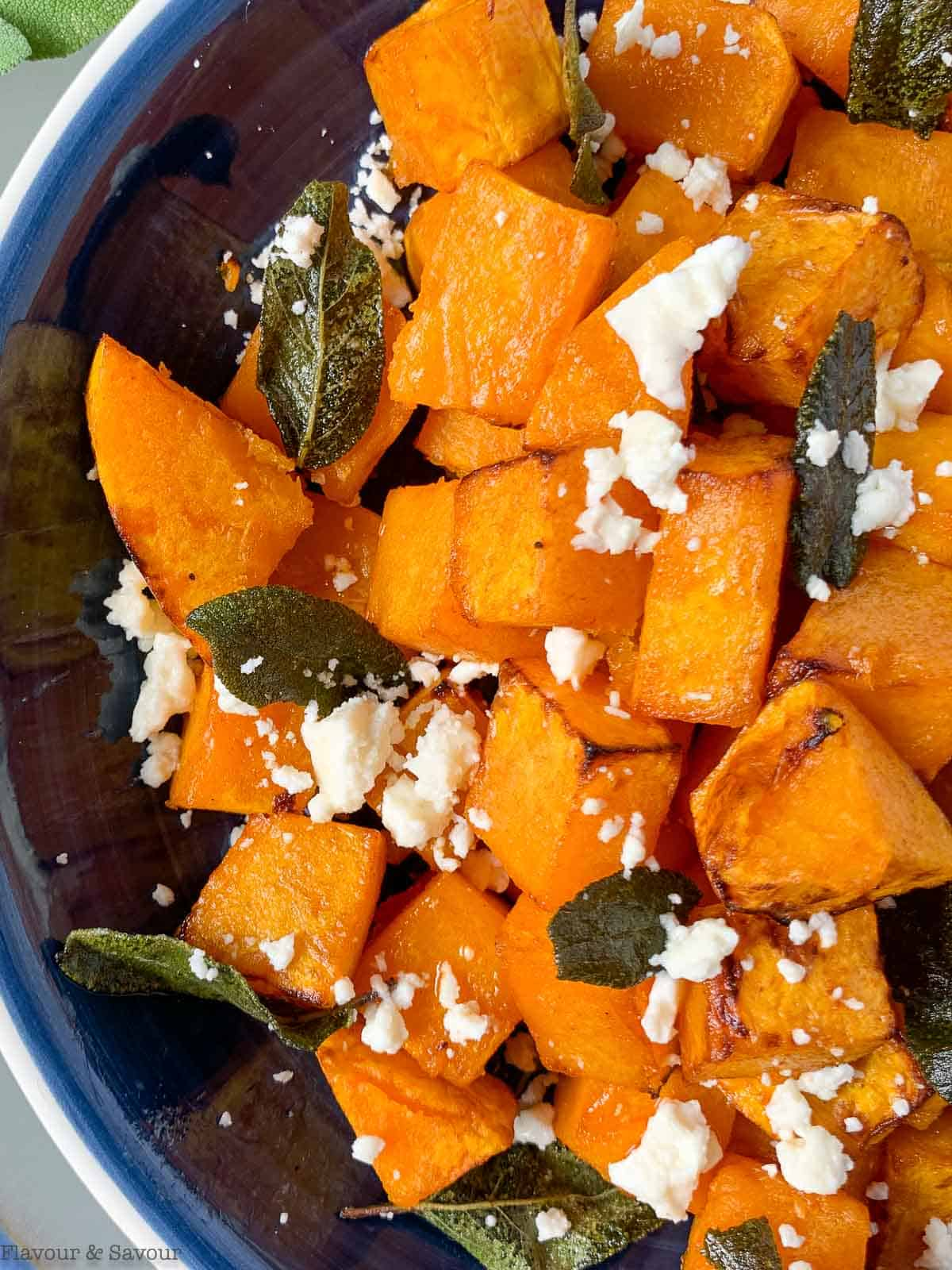 close up view of Butternut squash cubes in a blue bowl with feta cheese and sage leaves