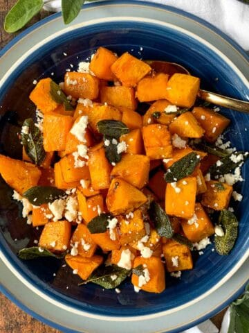A bowl of cubed butternut squash with feta cheese and sage leaves