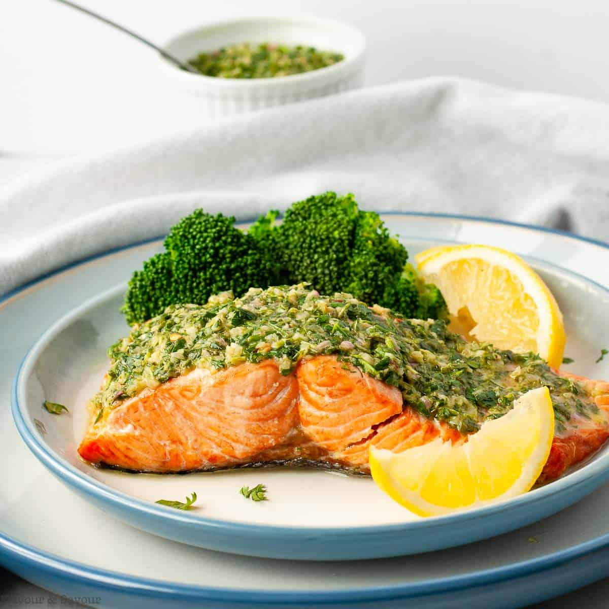 A salmon fillet cooked in an air fryer topped with chimichurri sauce served with lemon wedges.