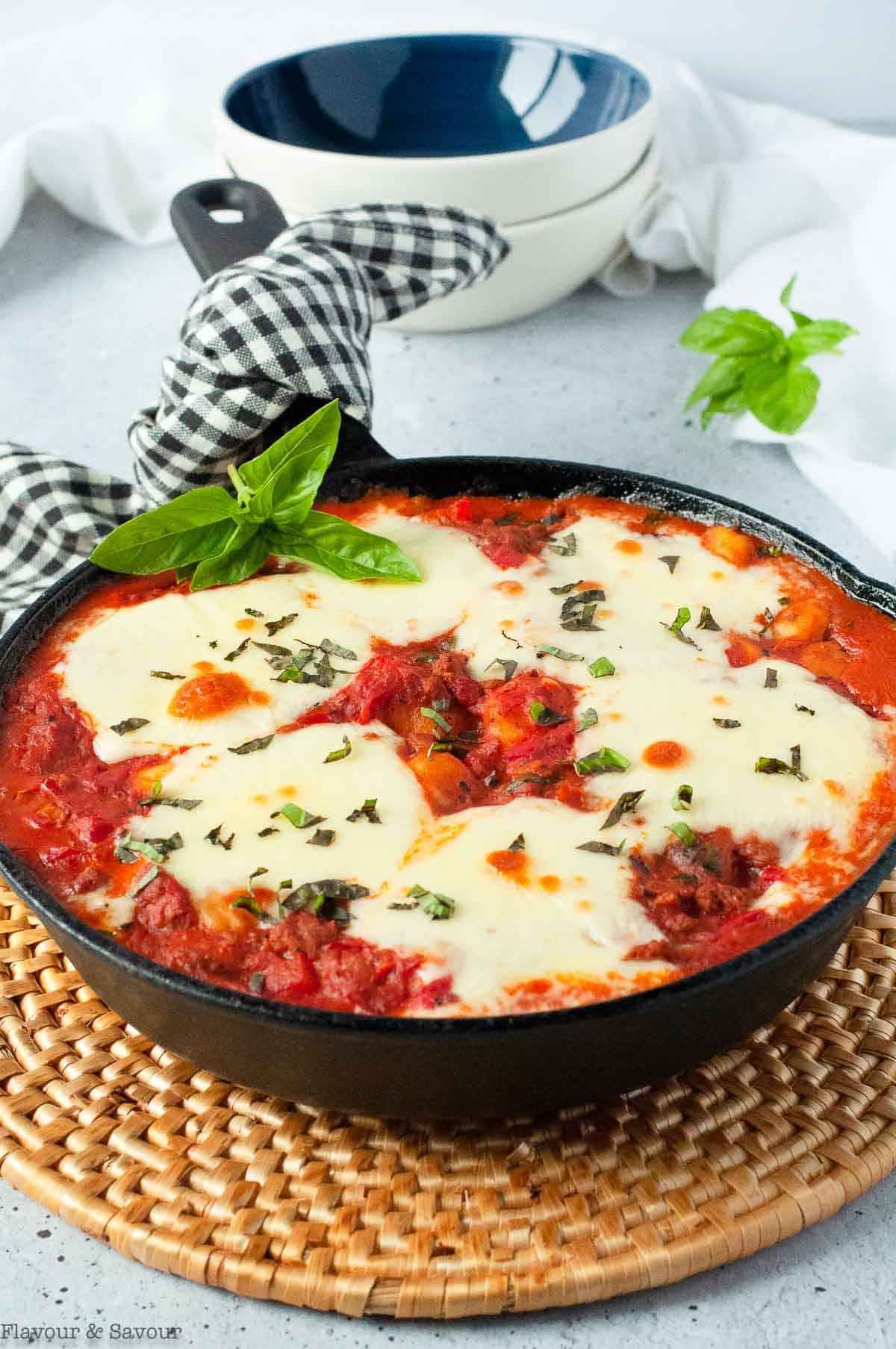 Skillet with baked gnocchi with tomatoes and cheese on a hot pad.