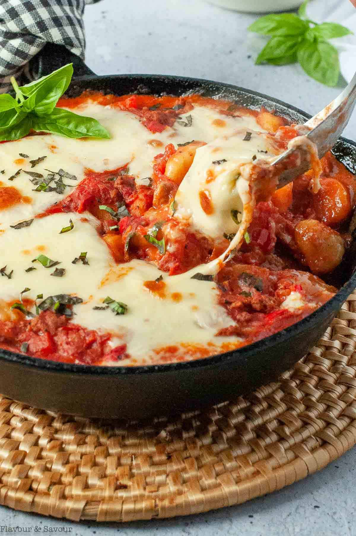 A serving spoonful of creamy tomato gnocchi bake with plant-based meat