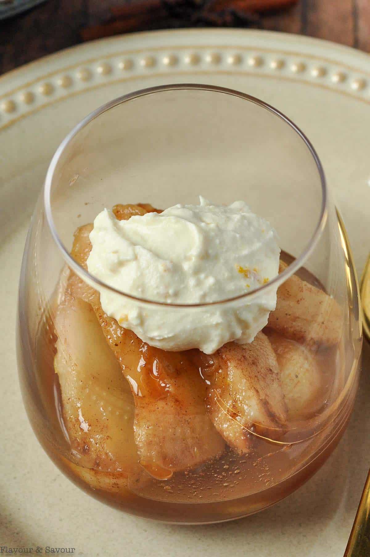 Poached cinnamon orange pears with mascarpone in a dessert glass.