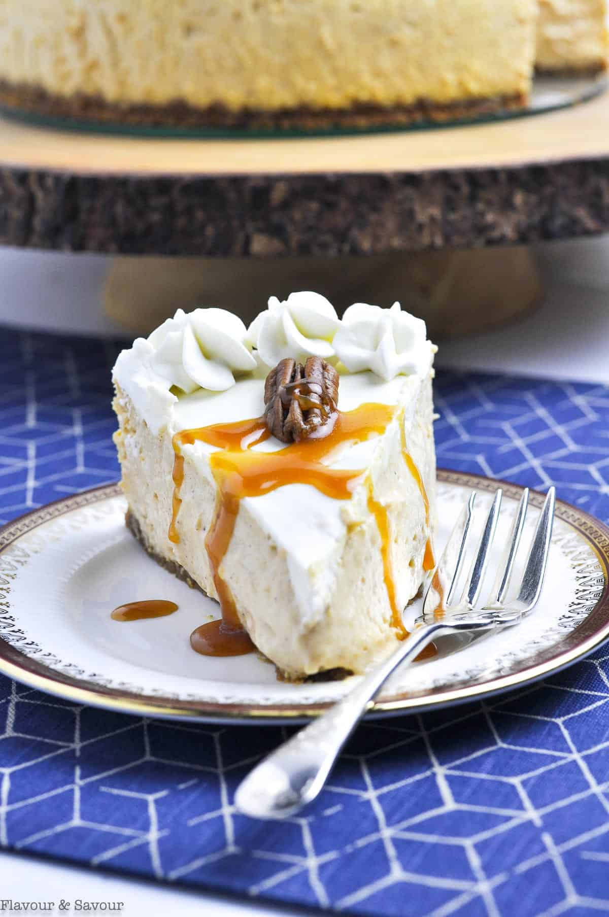 a slice of pumpkin cheesecake garnished with whipped cream and caramel sauce