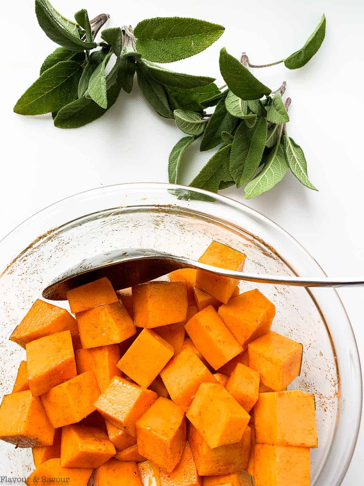 Butternut squash cubes in a bowl with fresh sage leaves beside.