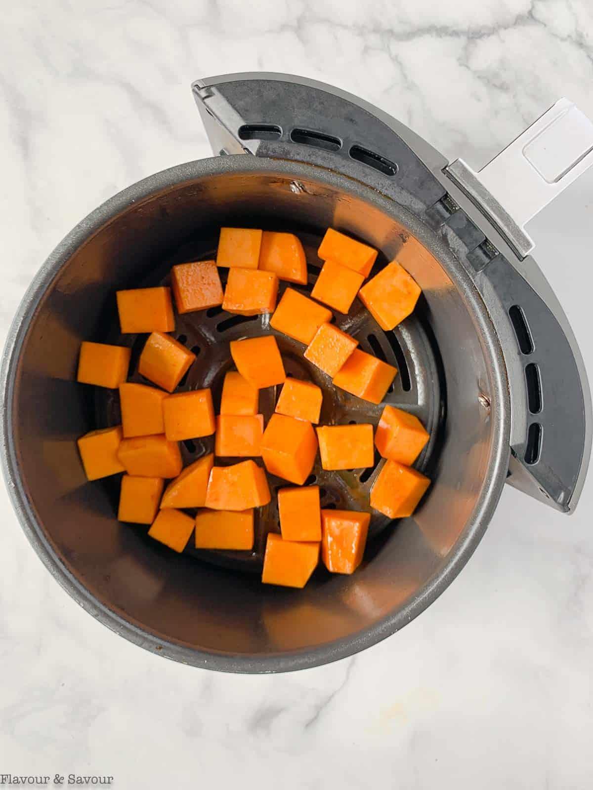 butternut squash cubes in an air fryer basket