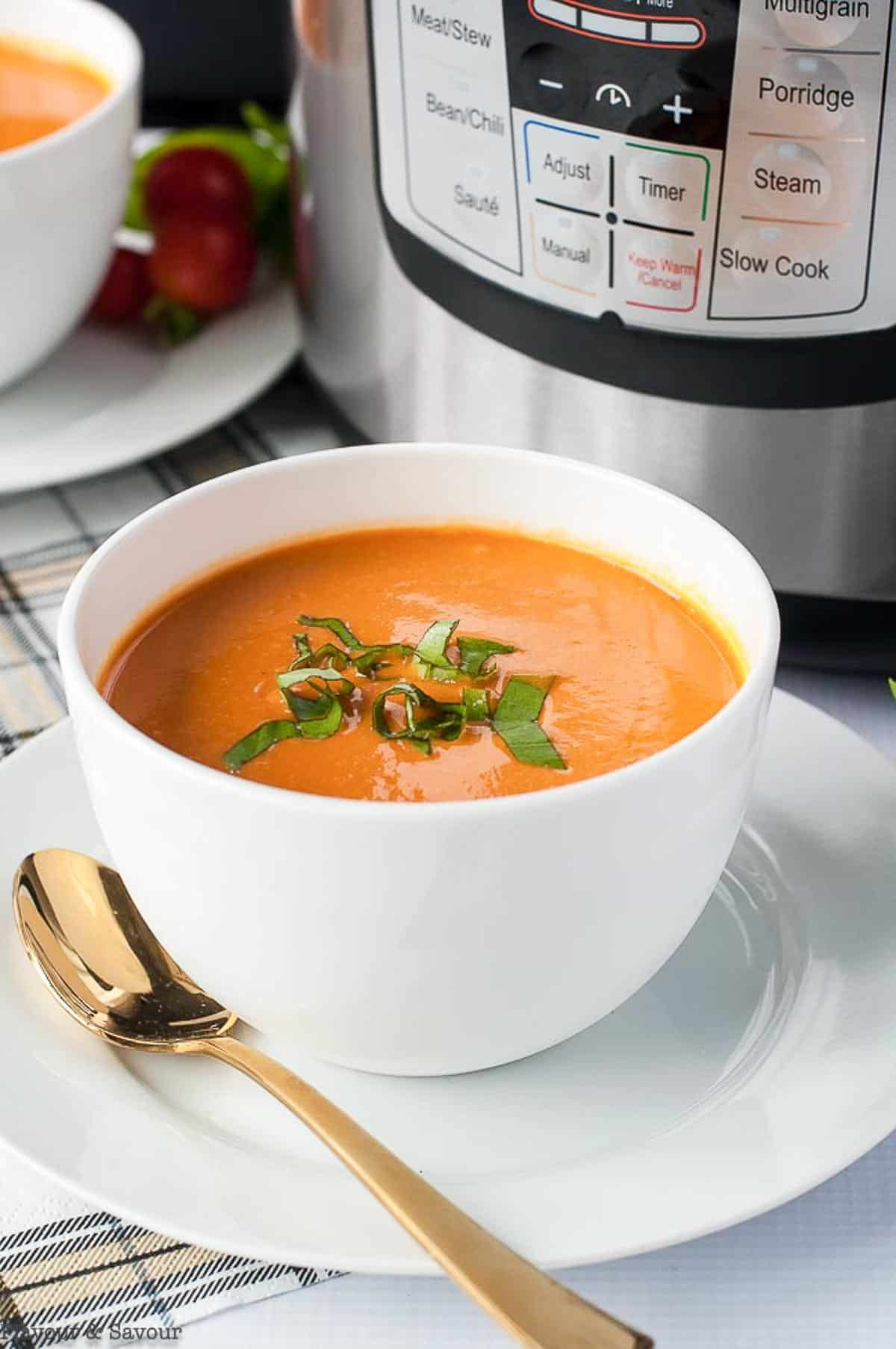 a bowl of creamy tomato soup beside an Instant Pot
